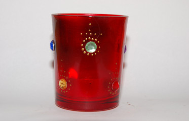 red candle light holder with decorations and cross