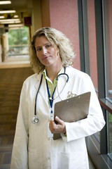 female medical professional with clipboard in hall