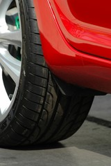black tyre of a red car closeup - focus on car