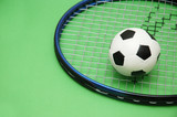 football and tennis racket on green background