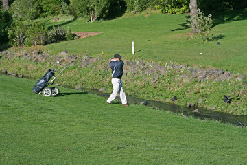 golf player swinging across a river