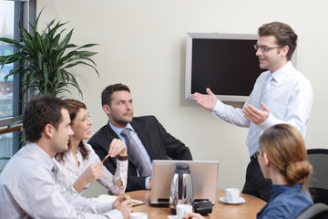 man making presentation  the group in an office