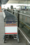 row of luggage carts with blank billboard poster