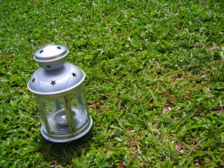 silver christmas lamp on green grass background