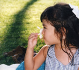 pretty girl smelling a flower - cropped poster