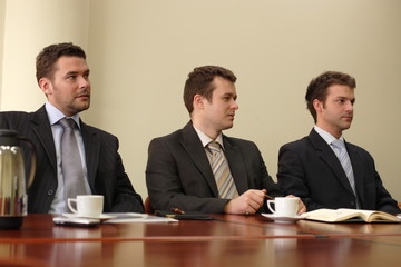 group of three business men sitting at the table
