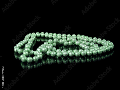 string of green pearls isolated on black with reflection