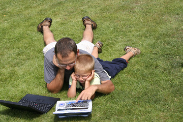 father and son working on laptops