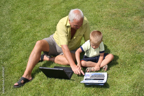 grandfather and grandson working on laptops