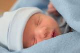 sleeping baby in blue blanket poster