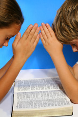 children praying over the bible vertical