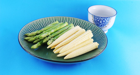 fresh asparagus shoots and corn on a plate