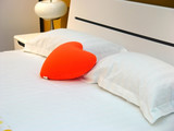 on the bed has a heart pillow poster