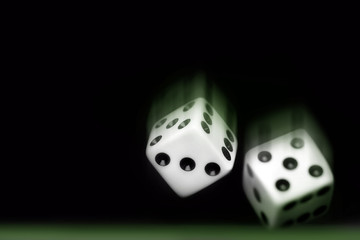 rolling two dices on black background