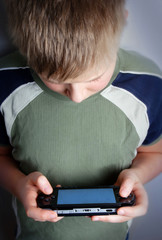 boys hand playing portable video game