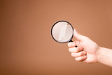 hand holding magnifying glass on the beige backgro poster
