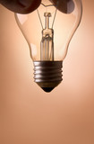 hand holding light bulb on the beige background poster