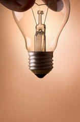 hand holding light bulb on the beige background