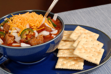 bowl of spicey chili and crackers with a spoon