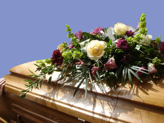 casket with flowers, blue sky