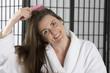 woman in a bath robe brushing her hair