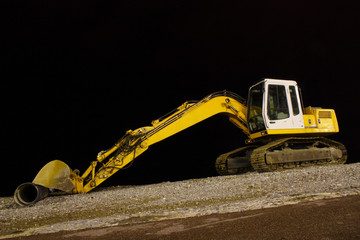 excavator on night pebble beach mounting tube