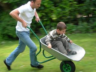 père poussant son fils dans une brouette