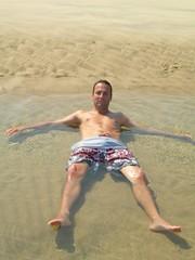 jeune homme baignant dans une flaque à la plage