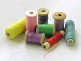 several bobbins of multi-color cotton threads poster