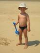 jeune garçon sur la plage avec une pelle