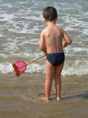 jeune garçon avec une épuistte au bord de l'eau