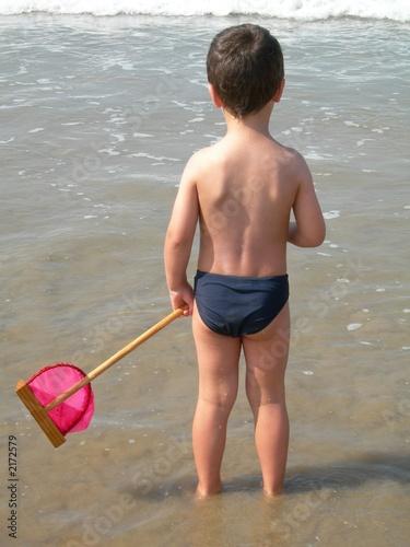 jeune garçon avec une épuisette au bord de l'eau