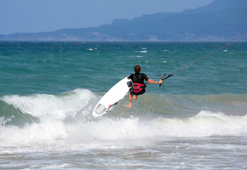 young male kitesurfer jumping on the sea
