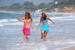 two young beautiful tanned women walking along san