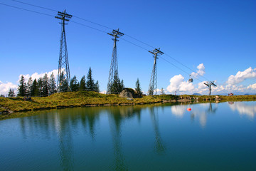 cable car summit with blue sky and lake reflection