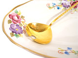 beautiful plate and golden spoon over white background