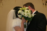 bride and groom kissing behind flower bouquet poster