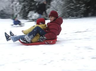geschwister beim rodeln im schnee
