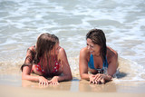 two attractive young women lying on a sunny beach