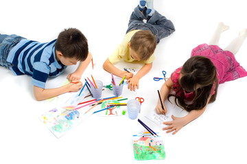 three children drawing on floor