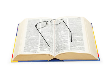spectacles over the open dictionary isolated on wh
