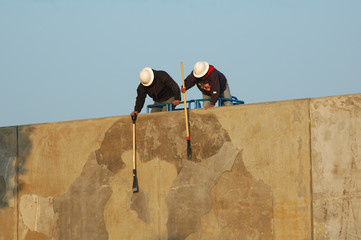 construction workers cleaning cement wall