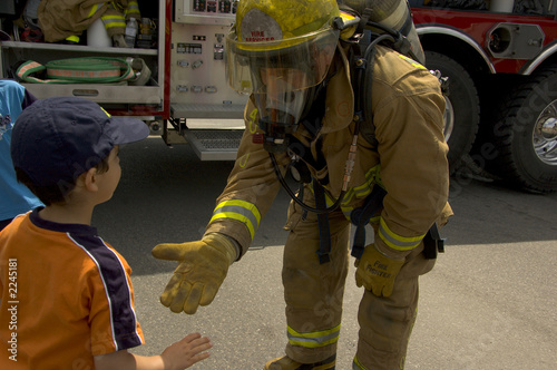Leinwanddruck Bild firefighter in uniform with a child