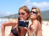 two pretty young girlfriends taking a photo of the