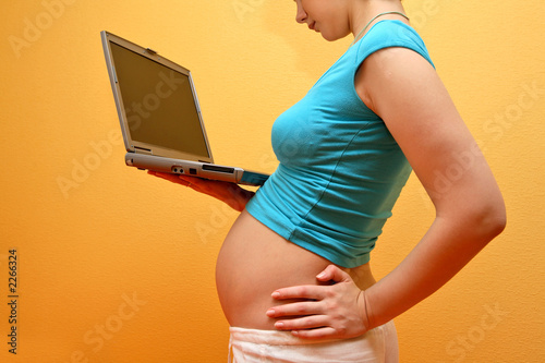 happy pregnancy - pregnant woman browsing on inter
