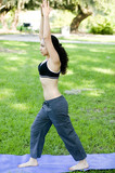 Hispanic woman practicing Yoga in the park poster