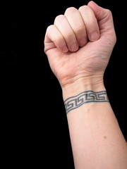 fist over wrist tattoo of greek key pattern