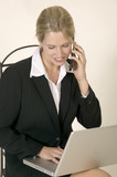 Blonde young business woman sitting and working on a lap top poster