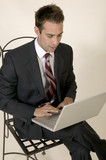 Young business man sitting working on a lap top poster