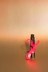 black perfume bottle and pink ribbon